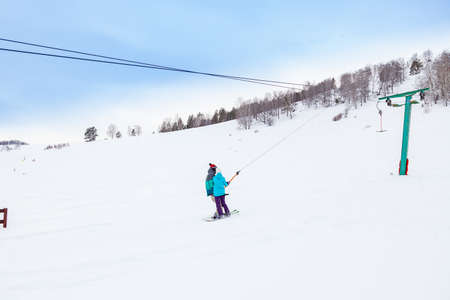 A couple of man and girl skier climbs a mountain through the white snow clinging to a rope of a tow rope in a sports tourist base Turquoise Katun. Seasonal sports. 版權商用圖片
