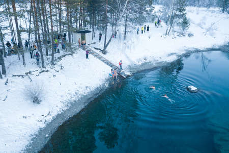 Altai, Russia - 03.01.2020: Aerial view of people bathing in an icy and cold blue lake with snow in the winter in the mountains during wellness and baptism. People walrus and health care. Zdjęcie Seryjne