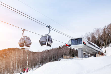 Upper passenger disembarkation point of a gondola cableway with a booth suspended on a rope on a background of mountains on winter sunset. Ski resorts and snowboarding.