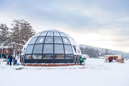 A beautiful cafe in the form of a hemisphere or a dome of glass and windows in winter with snow in the Altai mountains in the village of Manzherok. Stockfoto