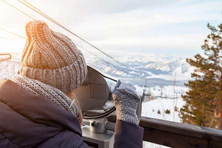 A young girl in a gray knitted hat looks through stationary binoculars on an observation deck in the alatai mountains in winter with snow.