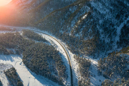 Aerial view of the paved road turning left in the mountains with conifers in winter with snow. Picturesque places and landscapes. Stok Fotoğraf