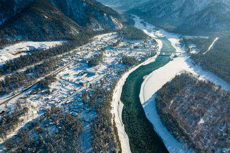 Picturesque landscape in the Altai mountains with snow-capped peaks under a blue sky with clouds in winter with green river and bridge for cars. White snow and calm.