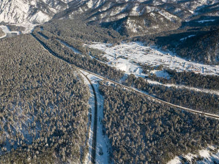 Aerial view of the paved road turning left with a crossroads in the mountains with conifers in winter with snow. Picturesque places and landscapes.