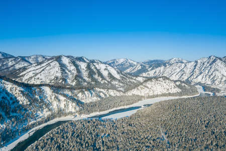 Picturesque landscape in the Altai mountains with snow-capped peaks under a blue sky with clouds in winter with green river Katun. White snow and calm.
