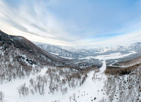 Aerial Picturesque panoramic landscape in the Altai mountains with snow-capped peaks under a blue sky with clouds in winter with gondola cableway and booths on ski resort. White snow and calm.