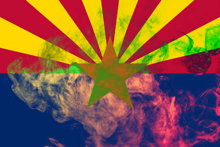 The national flag of the US state Arizona in against a gray smoke on the day of independence in different colors of blue red and yellow. Political and religious disputes, customs and delivery.