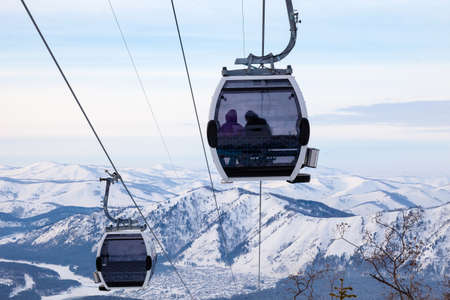 Cabin of a gondola cableway suspended on a rope where sits people with skis and snowboards high in the Altai mountains with snow and blue sky on winter sunset. Ski resorts and snowboarding.