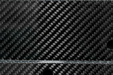 Close-up on interwoven carbon fiber lacquered in black and gray from heavy-duty yarn for the production of light and durable elements in industry. Banco de Imagens