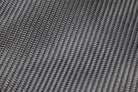 A close-up on a carbon fiber background of interwoven black and gray color from heavy-duty yarns for the production of light and durable elements in industry.
