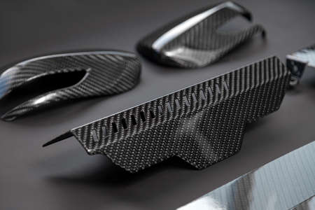 A close-up on a car exterior elements made from carbon fiber of interwoven black and gray color from heavy-duty yarns for the production of light and durable elements in industry. Tuning body parts.