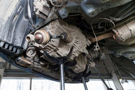 A car raised on a lift for repair and under it a detached engine suspended on a crane and a gear box on a lifting in a vehicle repair shop with view to the bottom in vehicle workshop. Auto service. Stock fotó