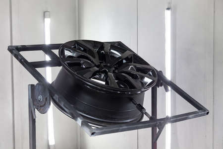 A black painted aluminum alloy wheel is mounted on a special frame during drying in a chamber in a vehicle body repair workshop. Auto service industry.