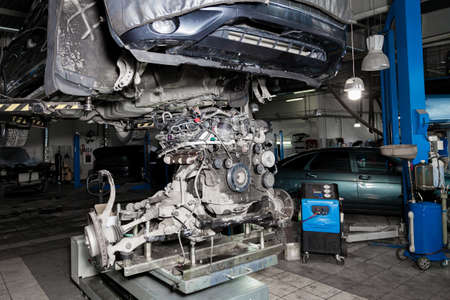 Replacement used engine on a table mounted under raised car on lift  for installation after a breakdown and repair in a vehicle workshop as a guarantee for the dealership. Auto service industry. Stock fotó