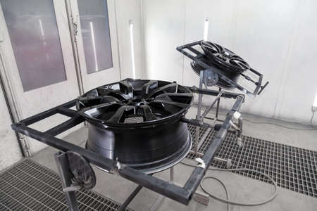 A Two black painted aluminum alloy wheel is mounted on a special frame during drying in a chamber in a vehicle body repair workshop. Auto service industry.