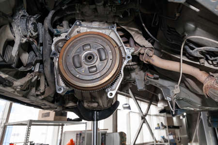 A car raised on a lift for repair and under it a detached Transmission gearbox suspended on a crane and a gear box on a lifting in a vehicle repair shop with view to the bottom in vehicle workshop.