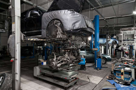Replacement used engine on a table mounted under raised car on lift  for installation after a breakdown and repair in a vehicle workshop as a guarantee for the dealership. Auto service industry. Stockfoto