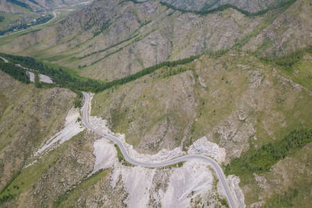 Aerial view of Serpentine Road Among Green Hills of Chike-Taman pass in Altai Mountains. Asphalt road going through cliff.