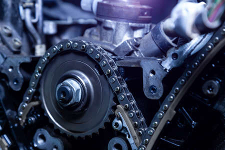Gear, chain drive shaft in conveyor, belt is on production line. Timing chain of car, tensioners in engine. Industrial roller chain, technology with selective focus. Team work in the office, business.