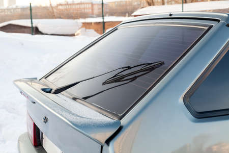 View to the rear window wiper that remove the melted snow and dirt from the windshield of the car during the day during the snow and rain with spoiler. Auto service and parts.
