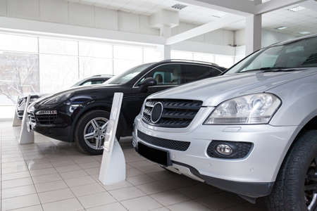 Many different used cars are in the dealership of a dealer accepted by the trade-in system during a sale in a bright room with large windows.