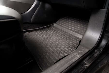 Dirty car floor mats of black rubber under passenger seat in the workshop for the detailing vehicle before dry cleaning. Auto service industry. Interior of sedan. Stock Photo
