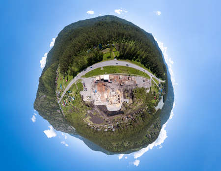 Aerial view of the construction site during the building of a wooden house from thick beams of sawn trees with equipment, tractors and trucks. Full VR 360 Degree Aerial Panorama Seamless Spherical. 写真素材