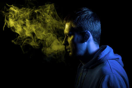 The man smoke an electronic cigarette on the dark background. Young man with beard vaping an electronic cigarette highlighted in yellow and blue. Vaper hipster smoke vaporizer.