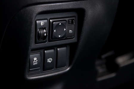 The button for the stability control system, side mirrors adjust and headlight washer on black panel of car near the steering wheel to overcome off-road, impassable roads and drive safely in snow or rain