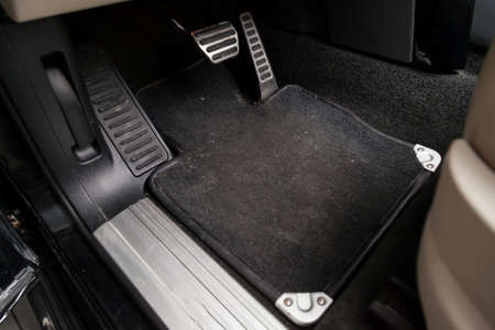 Dirty car floor mats of black carpet with gas pedals and brakes in the workshop for the detailing vehicle before dry cleaning Reklamní fotografie