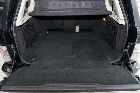 Open empty trunk of a car suv close-up before washing and vacuuming with a carpet floor mat of special black material ready for loading luggage. Auto service industry.