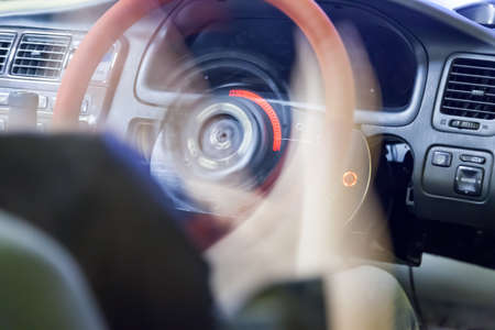 Steering wheel rotation with blur at a slow shutter speed in the passenger compartment during a drift race. Auto school and driving training.
