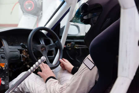 A professional racer in a black helmet and a white homologated suit sits in the sports seat of a car with a roll cage for drifting and racing during race and training. Stock Photo