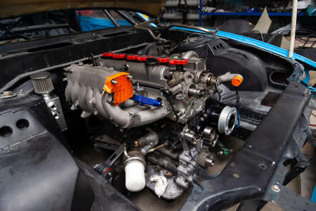 Powerful tuned gasoline engine with a turbocharger and a charger in the engine compartment of the car with an open hood in a car repair and improvement workshop. Banco de Imagens