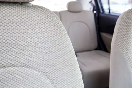 Upholstery of the seats of the passenger compartment of a luxury car with beige textile material in a workshop for hauling vehicles with a seam of thread. Banco de Imagens