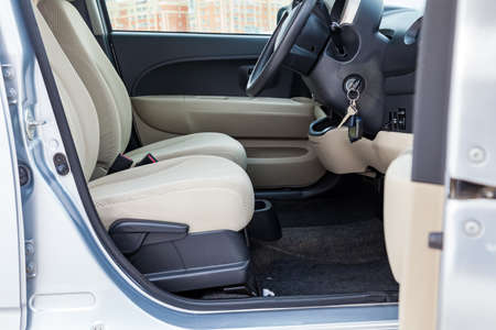 Comfortable front seats inside the car: the driver and passenger, tied with beige velourus, modern interior design, the steering wheel covered and a luxurious center console.