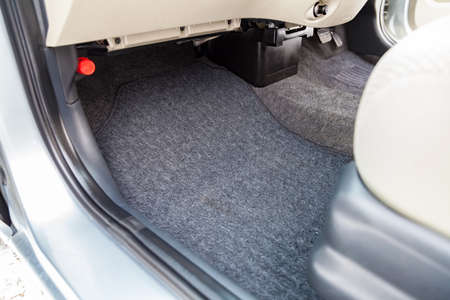 Clean car floor mats of black carpet under front passenger seat in the workshop for the detailing vehicle before dry cleaning. Auto service industry. Interior of sedan. Standard-Bild