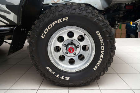 Novosibirsk, Russia - 02.26.2020: The most extreme all-season, off-road tire Cooper Discoverer STT Pro with AVM hubs off-road performance, tread design, tire durability on the wheel disk.