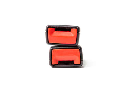 Two black plastic seat belt lock with red button on a white isolated background. Safety in the car during an accident.