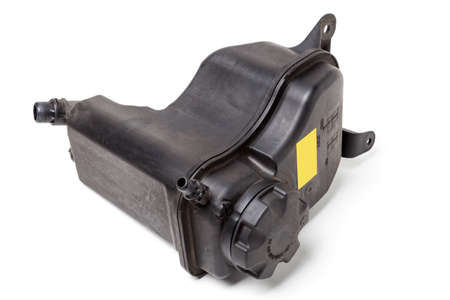 Coolant expansion tank in black on a white isolated background with a yellow nameplate. The unit of the liquid cooling system of internal combustion engines, the capacity of a special design.