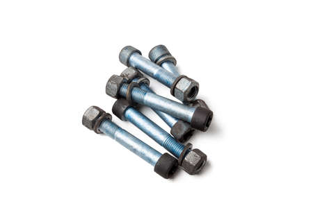 Metal car bolts with nuts used on a white isolated background in a photo studio. Spare consumables for auto repair in a garage or car service.
