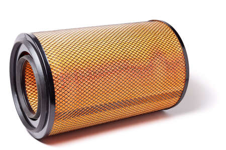 A coil of a new truck air filter made of orange material coated with black mesh cleans the air stream from contaminants before feeding it into the cylinders of an internal combustion engine.