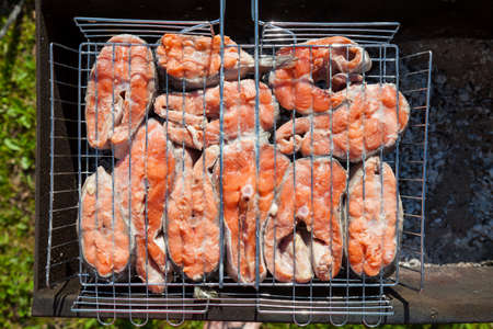 Closeup of steaks of red appetizing fish rich in saturated fatty acids, vitamins, iodine and phosphorus - coho salmon on the grill is grilled on charcoal in the barbecue. Imagens