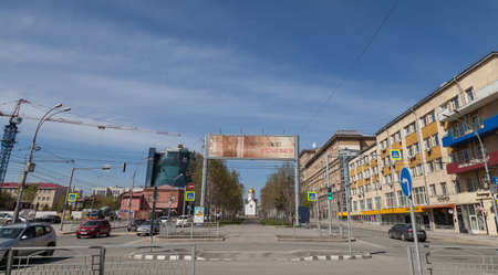 Novosibirsk, Russia - 04.26.2020: City landscape on old buildings mixed up with new ones, road with cars, transport and road signs separated by an alley with green trees and chapel, construction crane Stockfoto