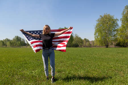 A girl in a black T-shirt and blue jeans stands in a Russian field with the American flag behind, holds it in her hands against the background of a green field and trees.