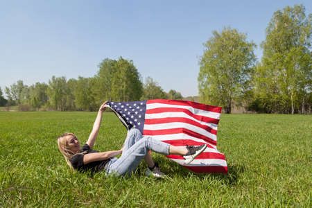 Russian girl blond is fooling around on the grass, lying down reclining, holding the developing flag of the United States of America in the hands of a deciduous forest of birches. Friendly hospitality