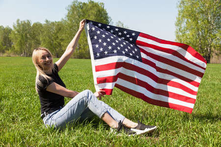 A Russian girl in a black T-shirt, blue jeans and sneakers sits on the green grass and holds in her hands the flag of the United States of America waving in the wind against the background of birches.