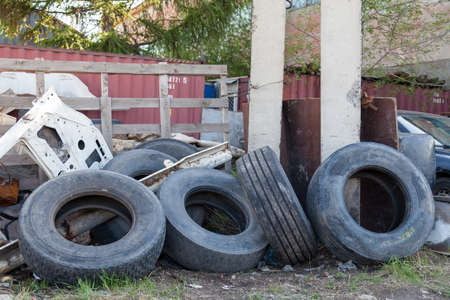 Automobile used rubber tires in a landfill near a concrete pillar against a background of green grass, trees, a metal cargo container and disassembled car bodies. Archivio Fotografico