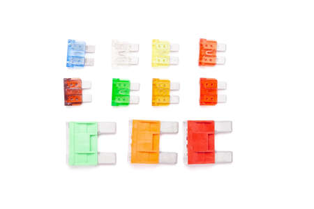 Colorful set of electronic fuses in yellow green orange red and blue on a white isolated background in a photo studio of a car electrical circuit protection device for sale or repair in auto service. Фото со стока