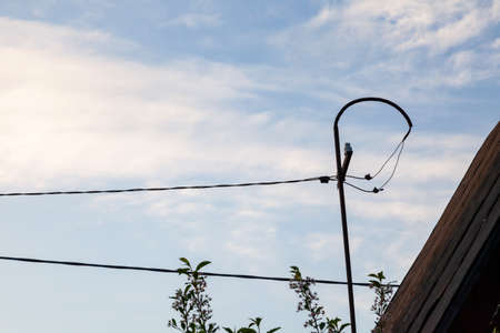 Old iron antenna made by yourself on the roof of the house against the blue sky and white clouds and wooden boards and stretched wires. A transmitter for receiving a radio or television signal. 版權商用圖片